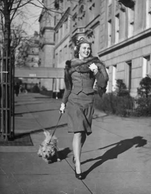 Actress-Joan-Caulfield-briskly-walking-her-West-Highland-terrier-Witty,-down-Fifth-Ave