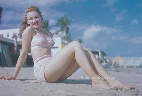 glamourdaze-woman-seated-on-beach-in-pink-bikini-1940