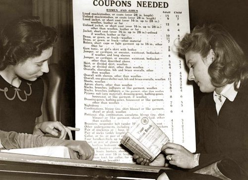 Two women study clothing coupon chart in 1942