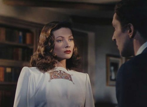 Gene Tierney in a white evening trouser suit suit with monogram-detail