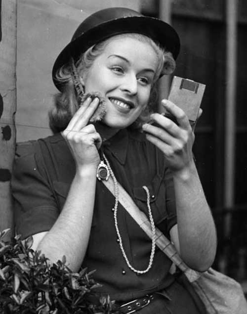 Air-raid-warden-Judy-McCrea-puts-on-some-make-up-while-on-duty-at-Paddington