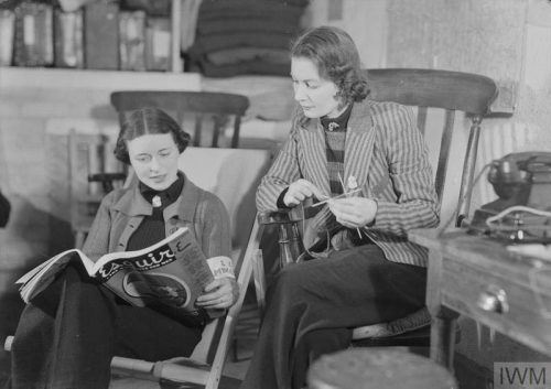 Two-off-duty-women-ambulance-drivers-relax-with-a-magazine-and-knitting
